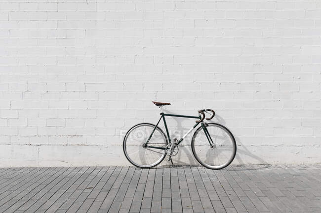 Racing cycle leaning against wall — Stock Photo