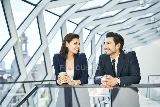 Smiling businesswoman and businessman having a coffee break in modern office — Stock Photo