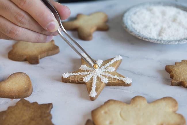 La mano del hombre decorando galleta de Navidad, de cerca - foto de stock