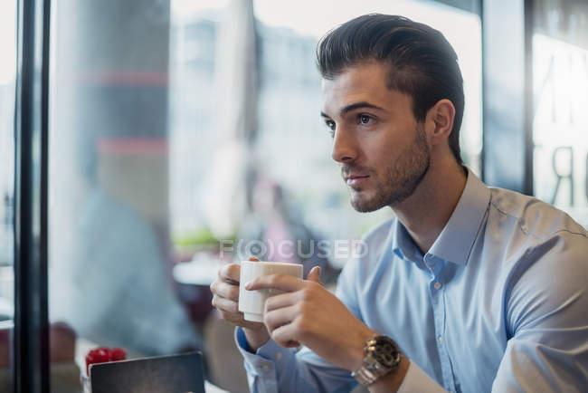 Giovane uomo d'affari che beve caffè in un caffè — Foto stock