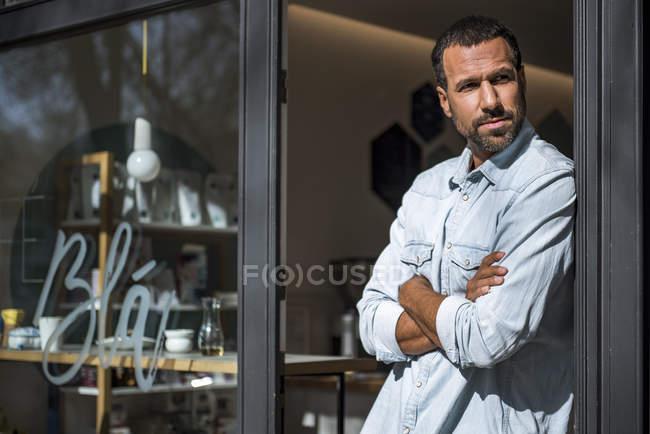 Человек у входной двери кафе оглядывается вокруг — стоковое фото