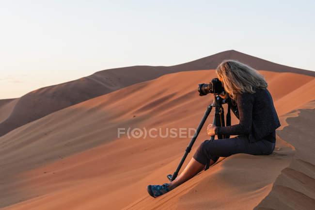 Afrique, Namibie, Désert namibien, Parc national du Naukluft, photographe photographiée tôt le matin, assise sur une dune de sable — Photo de stock