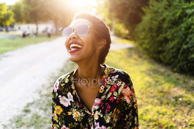 Laughing young woman wearing sunglasses outdoors at sunset — Stock Photo