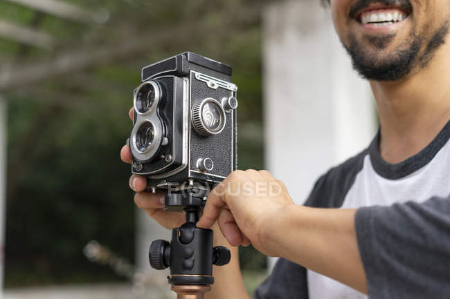 Close-up of happy young man using vintage camera — Stock Photo