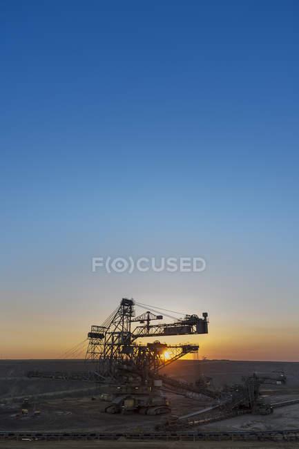 Allemagne, Rhénanie-du-Nord-Westphalie, Juechen, mine de surface Garzweiler, gerbeur au coucher du soleil — Photo de stock