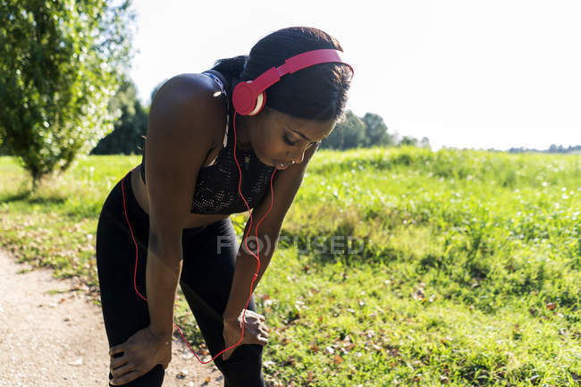 Young athlete in nature, listening music with headphones, preparing for training — Stock Photo
