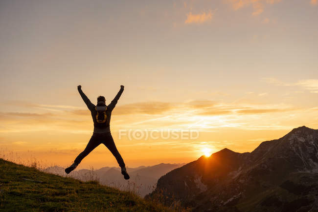 Man jumping in mountains at sunset — Stock Photo