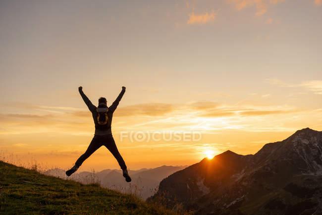 Человек прыгает в горы на закате — стоковое фото