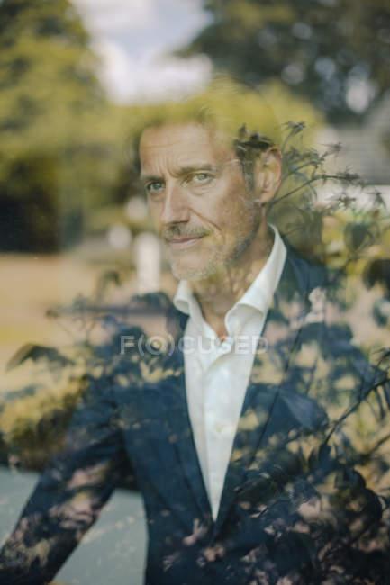 Porträt eines reifen Geschäftsmannes, der am Fenster steht — Stockfoto