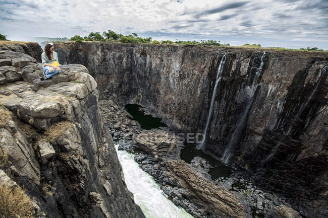 Zimbabwe, woman on rocks watching Victoria Falls — стокове фото