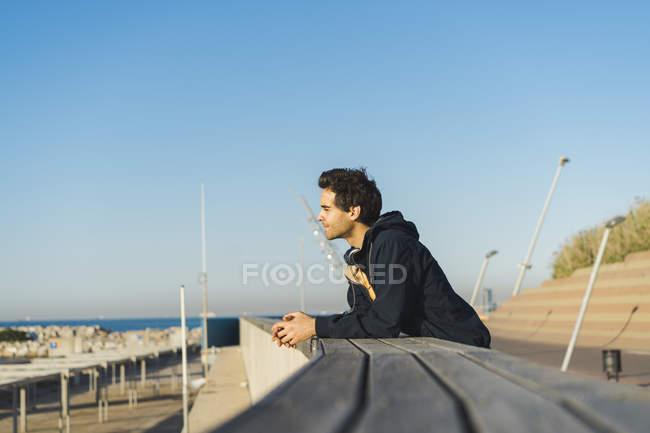 Homme avec des écouteurs se penchant sur le parapet, regardant la vue — Photo de stock