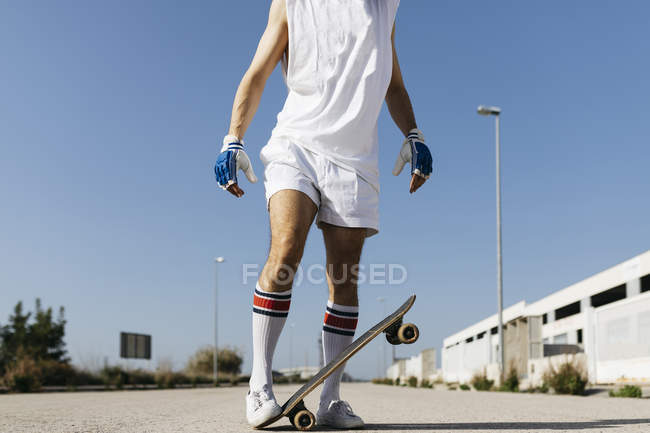 Man in stylish sportive outfit standing on skateboard upside down against blue sky — Stock Photo