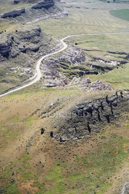 USA, Aerial of escarpments and cliffs bisected by a country road in Western Nebraska — Stock Photo
