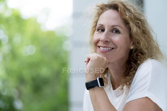 Portrait de femme souriante avec smartwatch en plein air — Photo de stock
