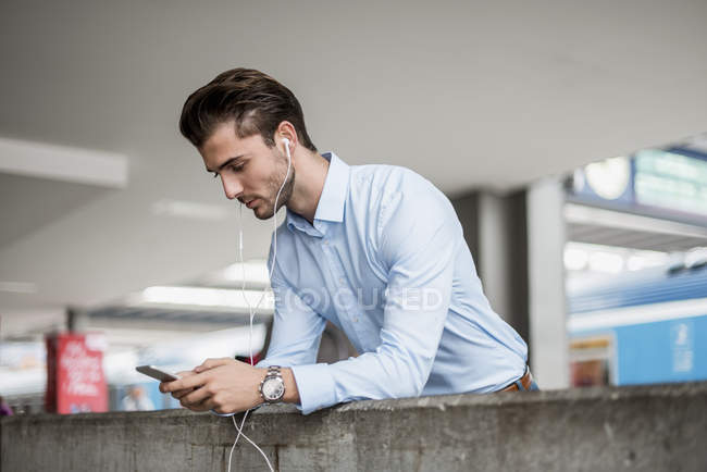 Businessman with cell phone and earbuds at the station — Stock Photo