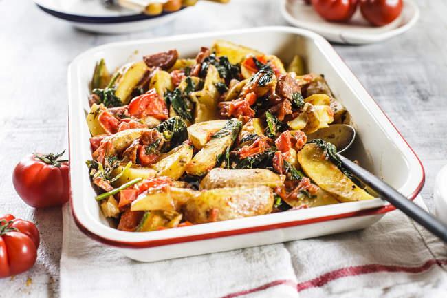 Casserole con patatas, espinacas, tomates y chorizzo - foto de stock