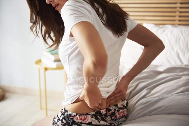 Frau sitzt mit Rückenschmerzen im Bett, Teilsicht — Stockfoto
