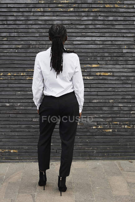 Back view of businesswoman with dreadlocks wearing white shirt and black trousers — Stock Photo