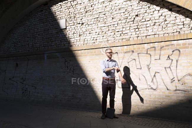 Бизнесмен стоит на улице и засучив рукава — стоковое фото