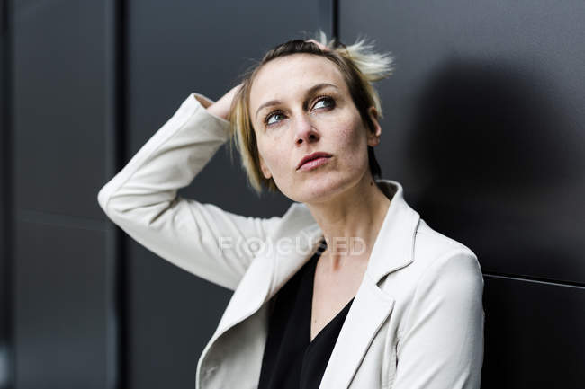 Portrait of pensive businesswoman looking up against black wall — Stock Photo