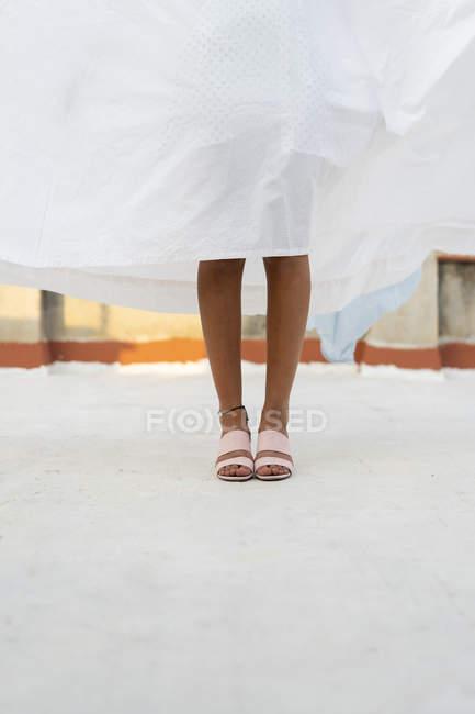 Piernas de mujer escondida detrás de la sábana de secado - foto de stock