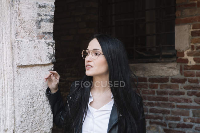 Young woman at old brick building looking around — Stock Photo