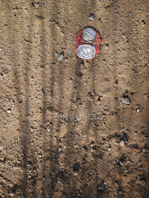 Crushed tin can on ground — Stock Photo