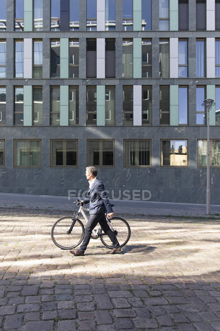 Mature businessman pushing bicycle in city — Stock Photo