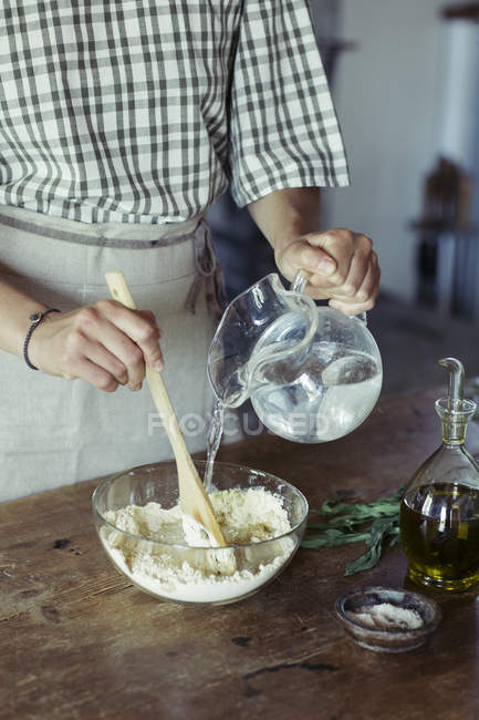 Young woman in kitchen preparing dough for fresh chickpea cake — Stock Photo