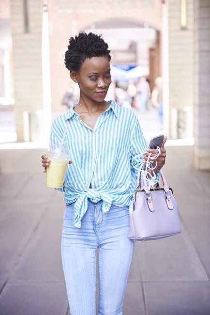 Femme avec smoothie regardant le téléphone portable dans la ville — Photo de stock