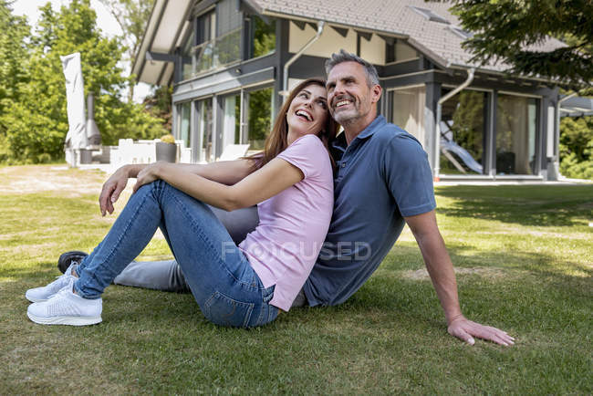Happy couple sitting in garden of their home — Stock Photo