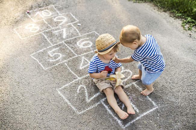 Niño pequeño alimentándose de su hermana pequeña - foto de stock