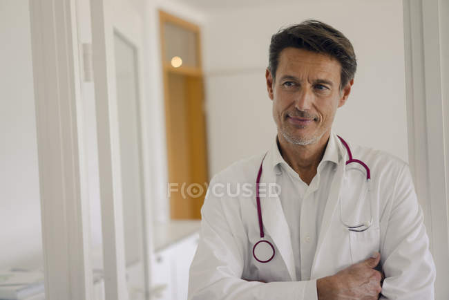 Médico de pie en el hospital con los brazos cruzados, retrato - foto de stock