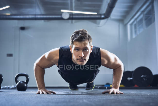 Спортивный человек делает упражнения отжимания в тренажерном зале — стоковое фото