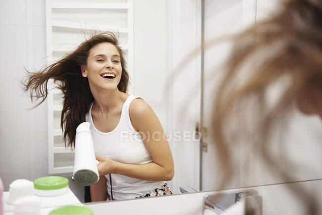 Immagine a specchio di una donna che ride asciuga i capelli in bagno — Foto stock