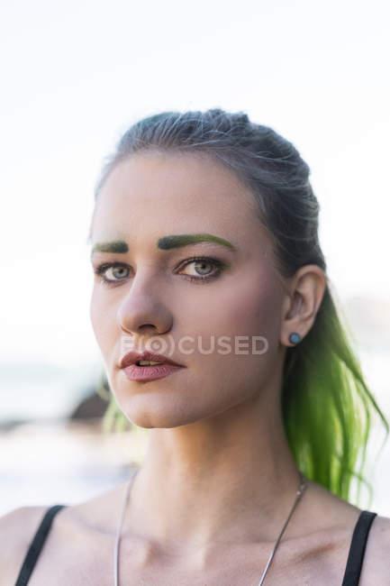Портрет молодой женщины с окрашенными зелеными бровями и волосами — стоковое фото
