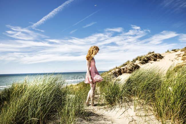 Netherlands, Zandvoort, woman standing in dunes — стокове фото