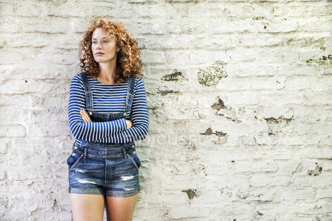Portrait of young woman with arms crossed leaning against white brick wall — Stock Photo