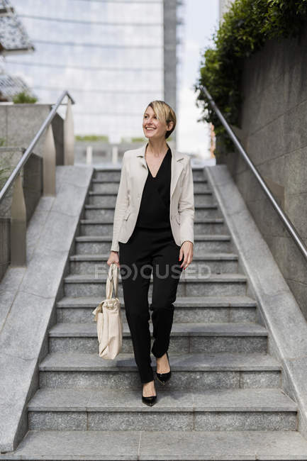 Smiling businesswoman walking downstairs in city — Stock Photo