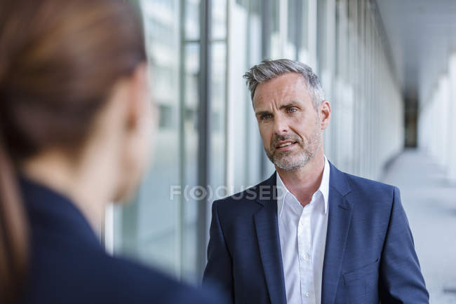 Portrait of sceptical businessman face to face to his business partner — стокове фото