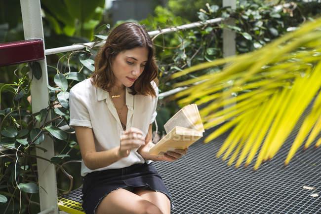 Молодая женщина в теплице, читает книгу — стоковое фото