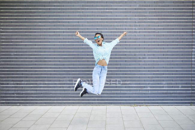 Счастливая женщина, прыгающая в воздух перед серым фасадом — стоковое фото