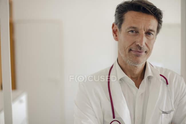 Médico de pé no hospital com estetoscópio ao redor do pescoço, retrato — Fotografia de Stock