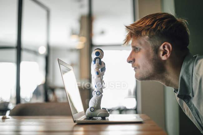 Hombre mirando robot de juguete, de pie en la computadora portátil - foto de stock