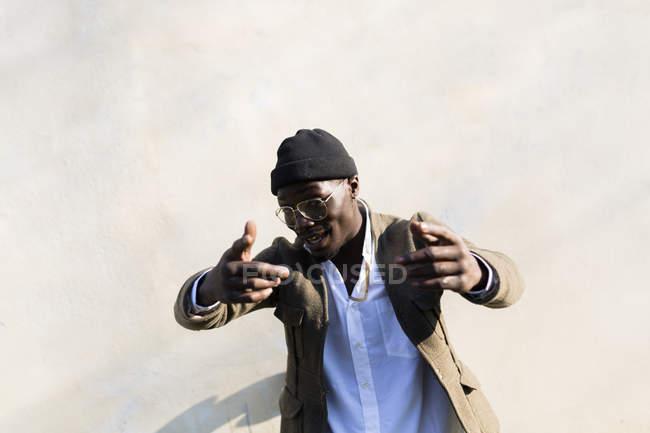 Jovem em chapéu de lã gestando na frente da parede — Fotografia de Stock