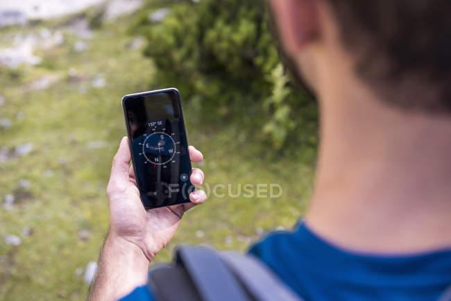 Randonneur utilisant l'application de boussole dans la nature — Photo de stock