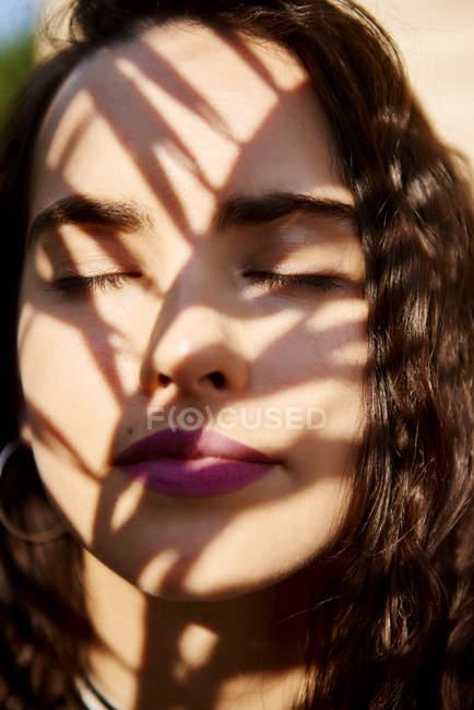 Cara de mujer joven a la luz del sol - foto de stock