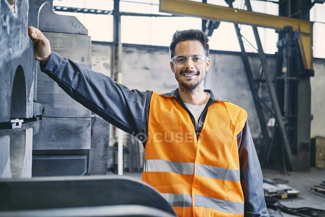 Portrait of smiling man wearing protective workwear in factory — Stock Photo