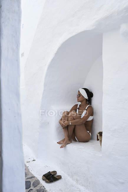 Молодая женщина в белом бикини сидит в стене нишу — стоковое фото