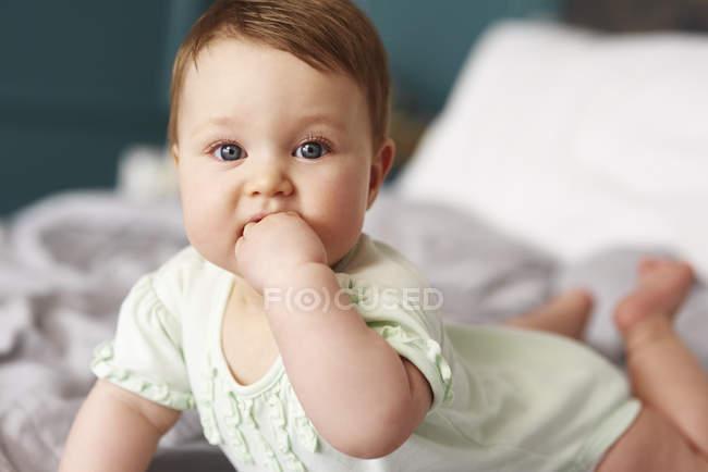 Retrato do bebê que encontra-se na cama em casa — Fotografia de Stock